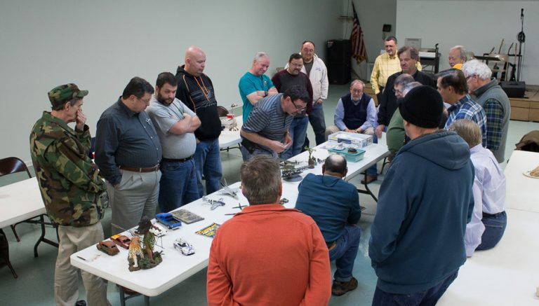 A group of diverse scale modelers discussing models on display.